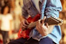 传牛仔衬衣弹电吉他的男青年